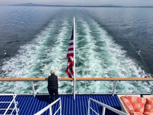 quirky-cruise-pacific-northwest-aboard-american-constellation-woman-standing-on-stern-overlooking-water-wake