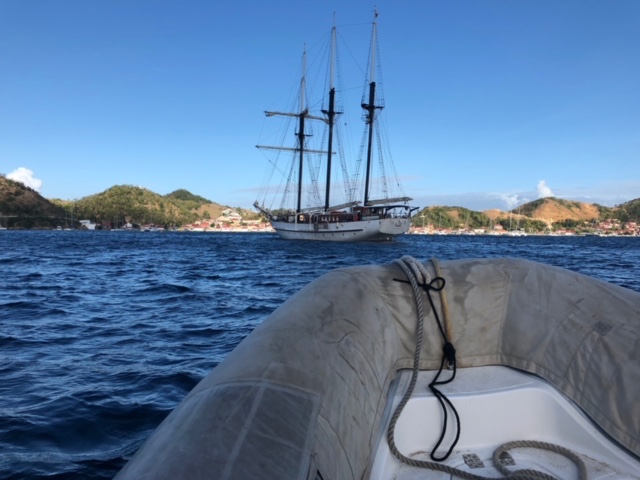 Island Windjammers' Caribbean Sailing Adventure view of the ship from aboard the dinghy in the water