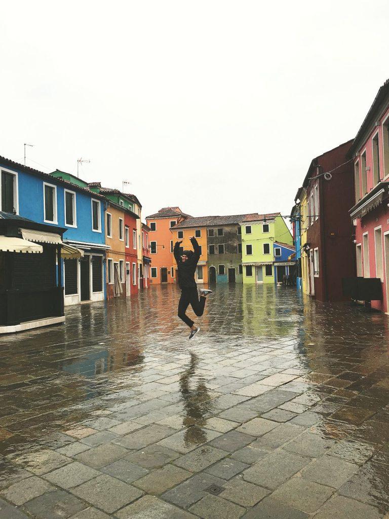 Dana jumping in the rain on a Venice Lagoon cruise