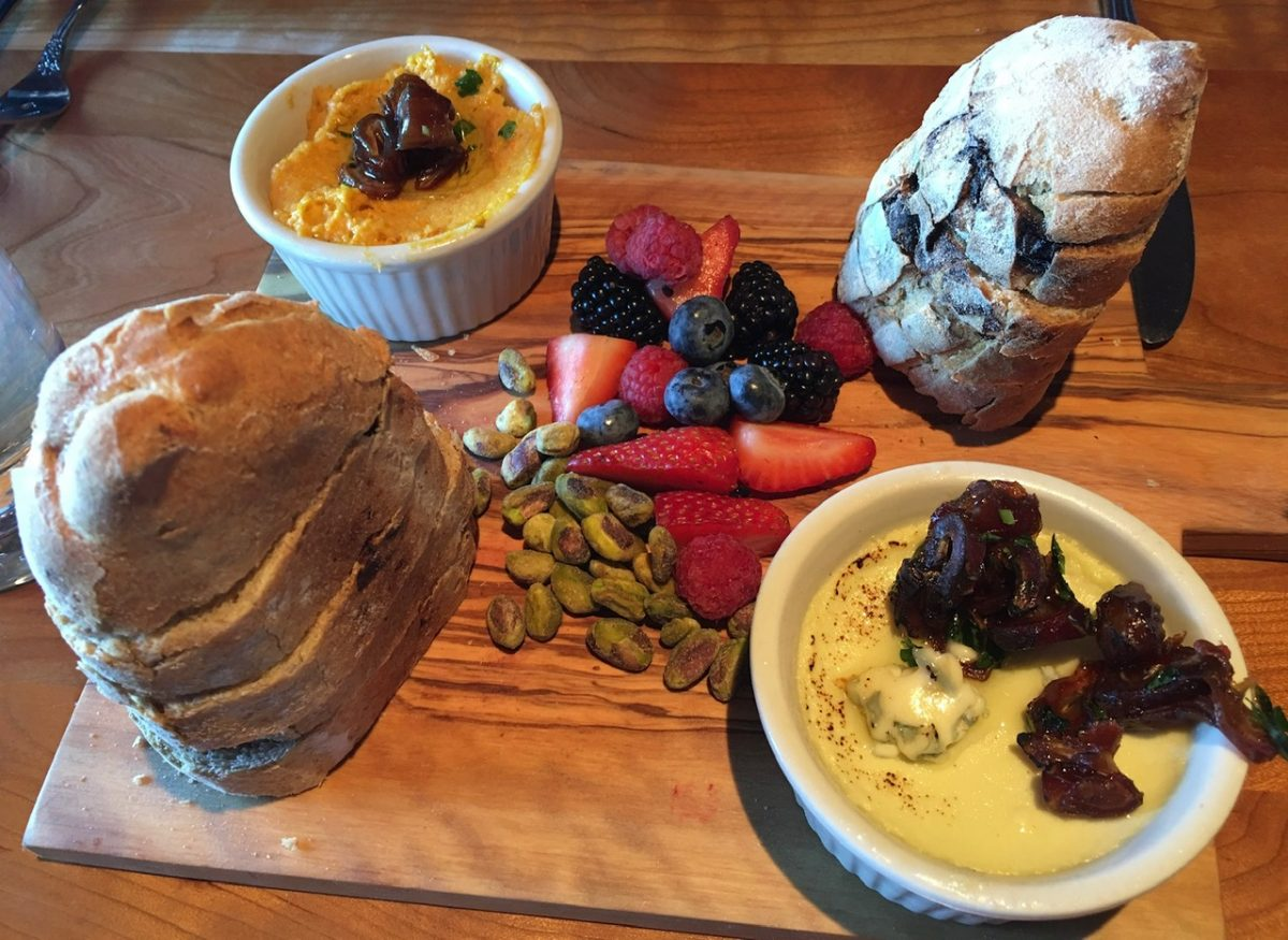 An appetizer shared board with blue cheese, date topping, carrot butter, fruit, nuts and fig bread