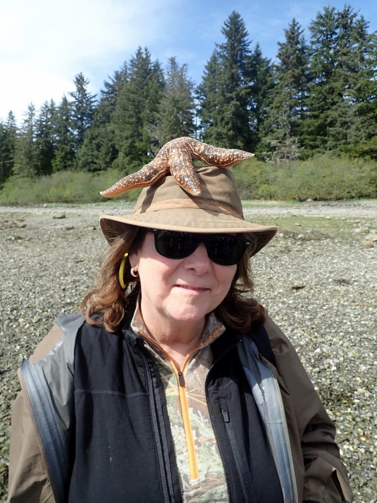 Giant starfish on Judi's hat before bushwacking trek.